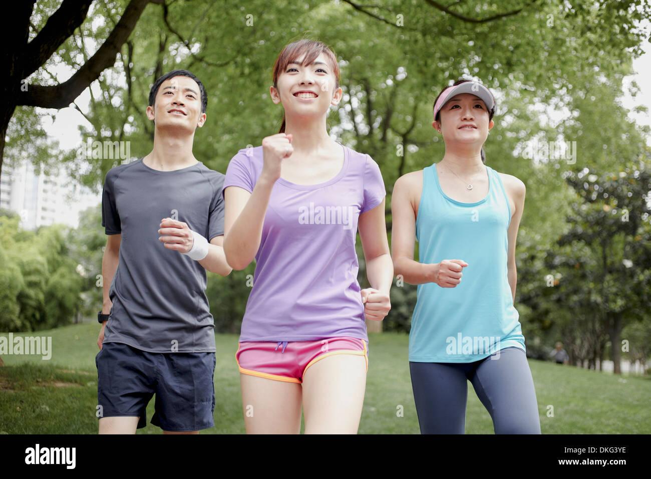 Tre giovani a fare jogging nel parco Immagini Stock