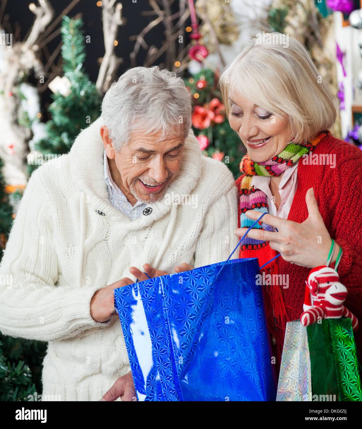 Sorpreso giovane cercando in borsa per la spesa Immagini Stock