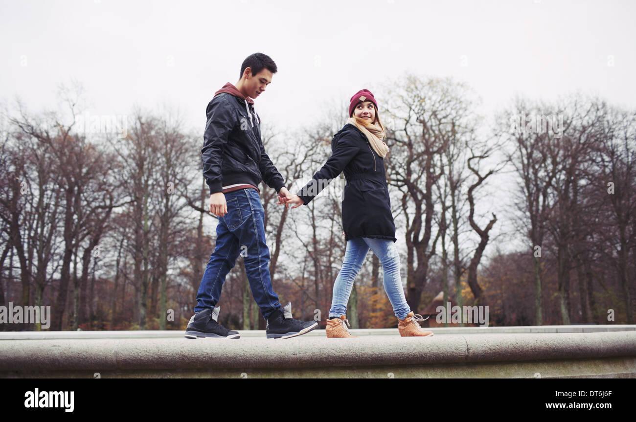 Basso angolo vista del bel giovane uomo con la sua ragazza camminare insieme tenendo le mani nel parco. Razza mista Immagini Stock