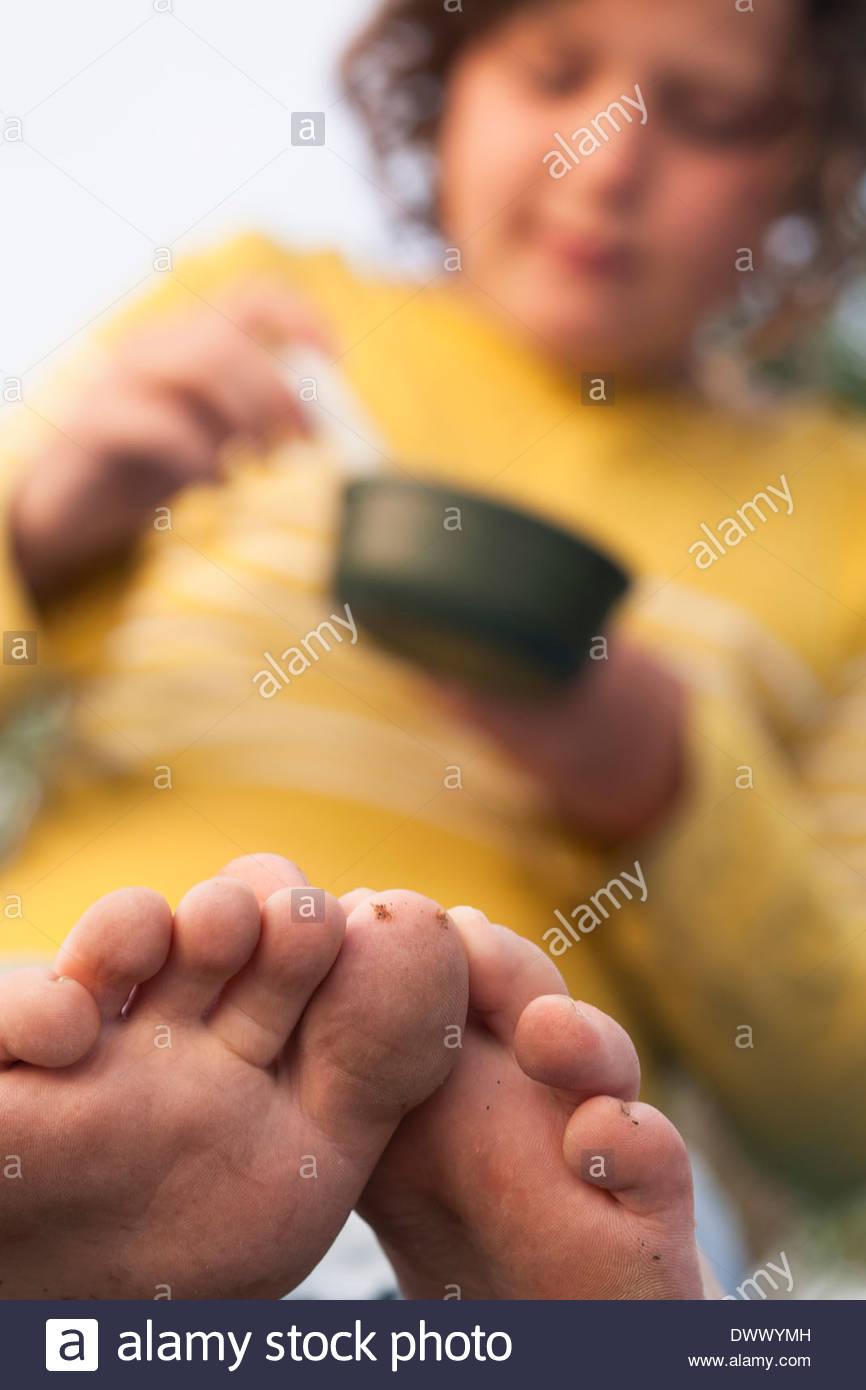 Ragazza giovane mangiare con focus su piedi Immagini Stock