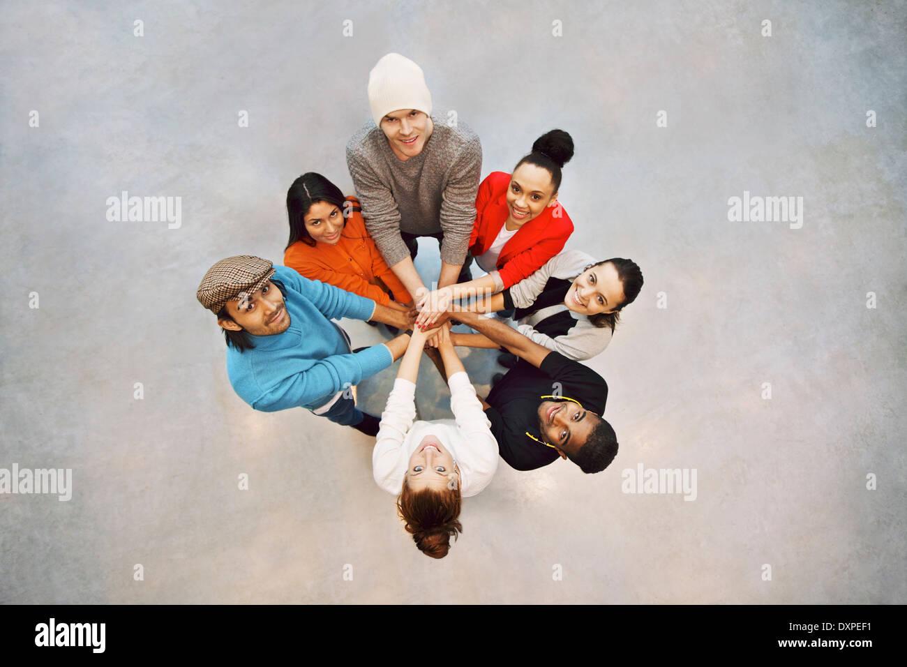 Gruppo di felice giovani studenti che mostra. Vista superiore del gruppo multietnico di giovani mettendo le mani Immagini Stock