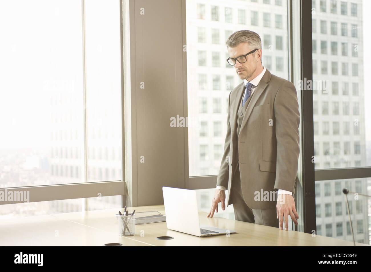 Imprenditore guardando giù al laptop sulla scrivania in ufficio Immagini Stock