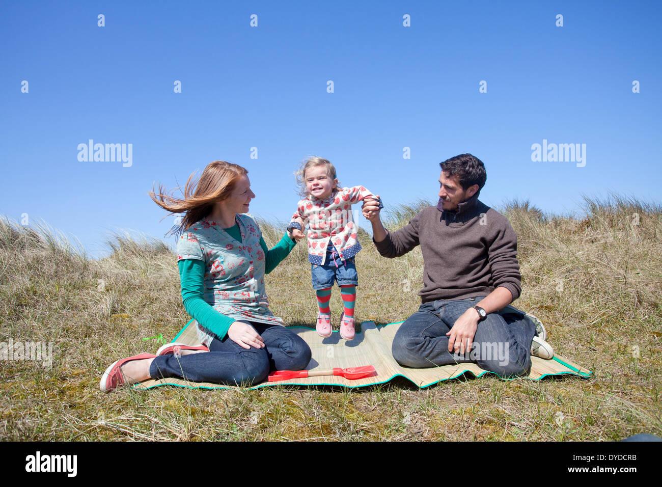 Una giovane famiglia avente il divertimento sulle dune di sabbia a Horsey spiaggia sulla costa di Norfolk. Immagini Stock