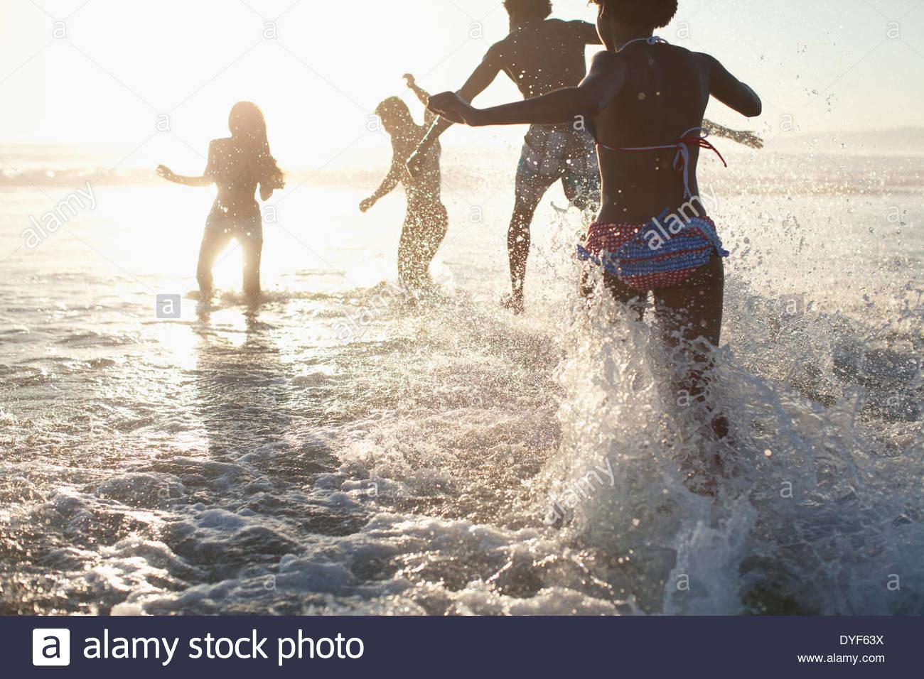 Amici a giocare in onde sulla spiaggia Immagini Stock