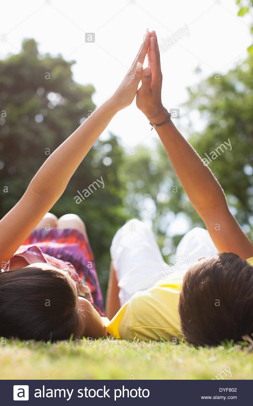Gli adolescenti che stabilisce in erba tenendo le mani Immagini Stock