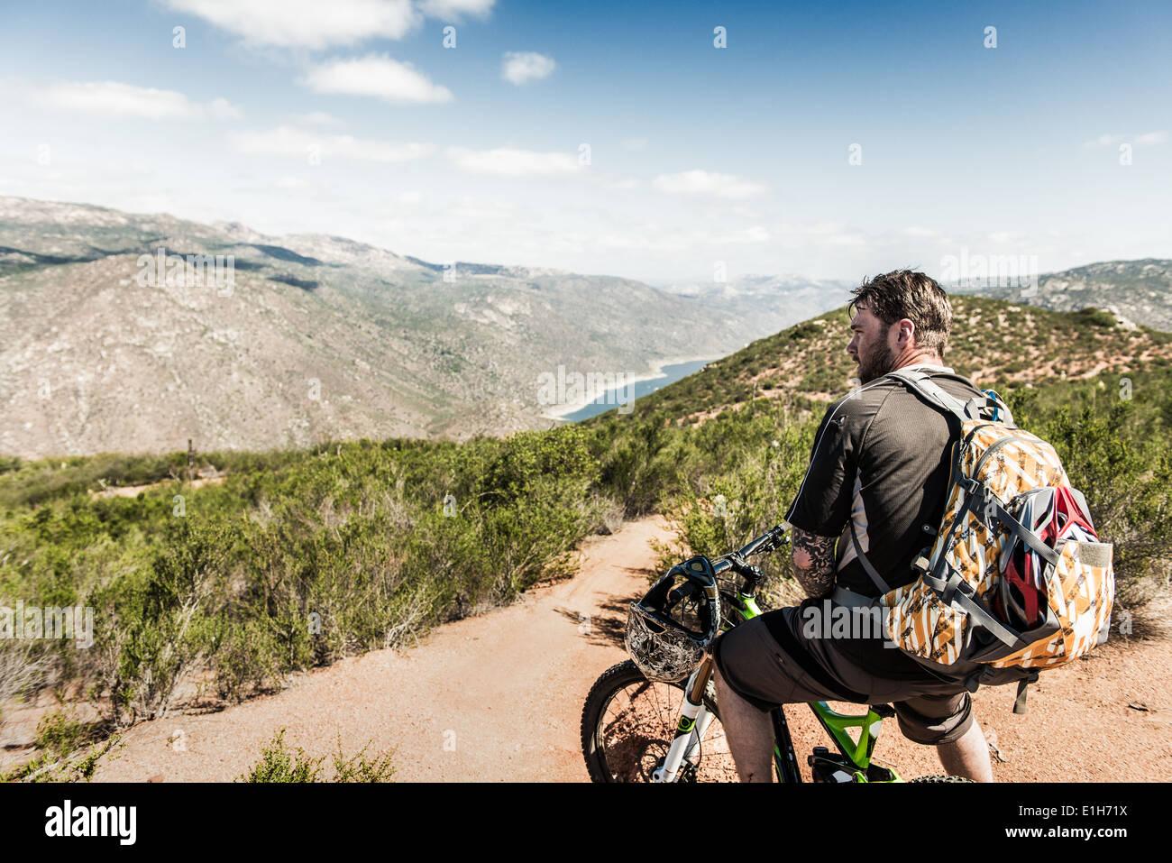 Downhill mountain biker guardando a vista Immagini Stock