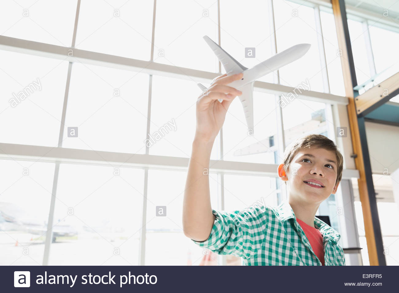 Ragazzo giocando con aeroplano giocattolo in aeroporto Immagini Stock