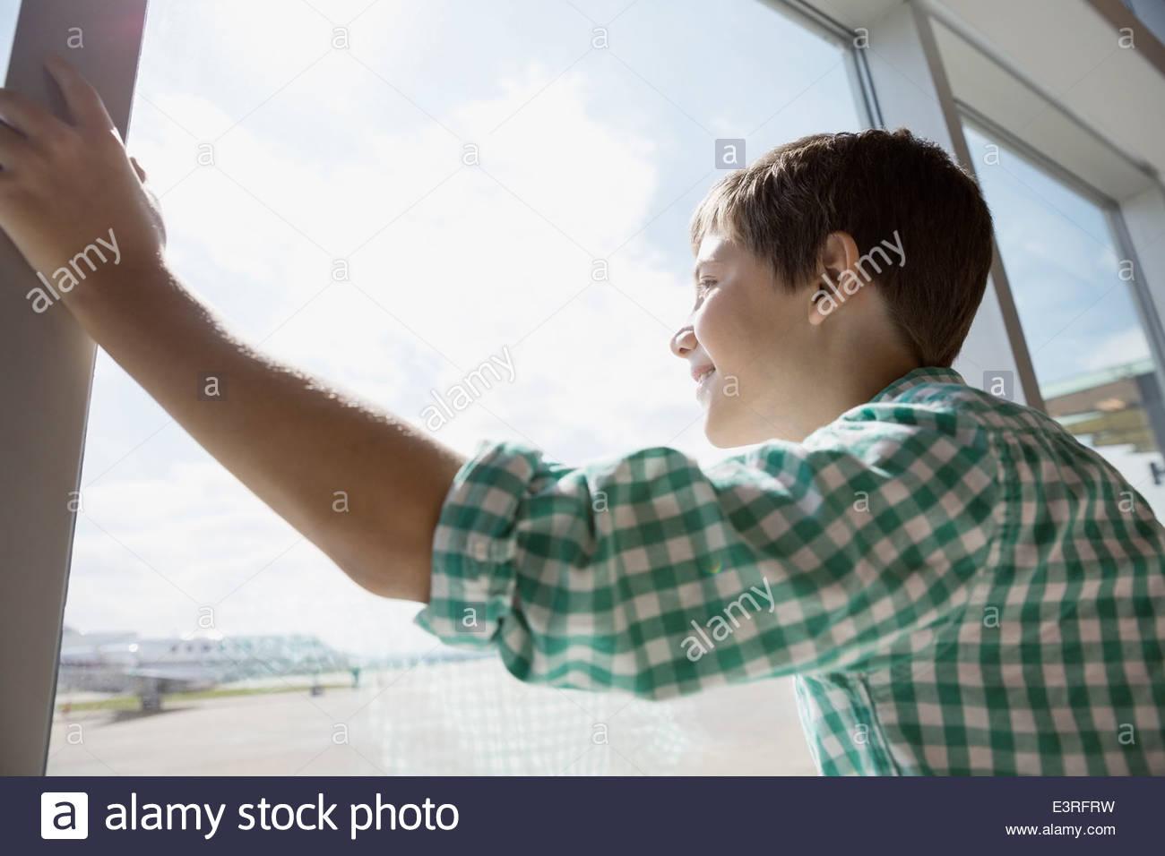 Ragazzo che guarda alla finestra di airport Immagini Stock