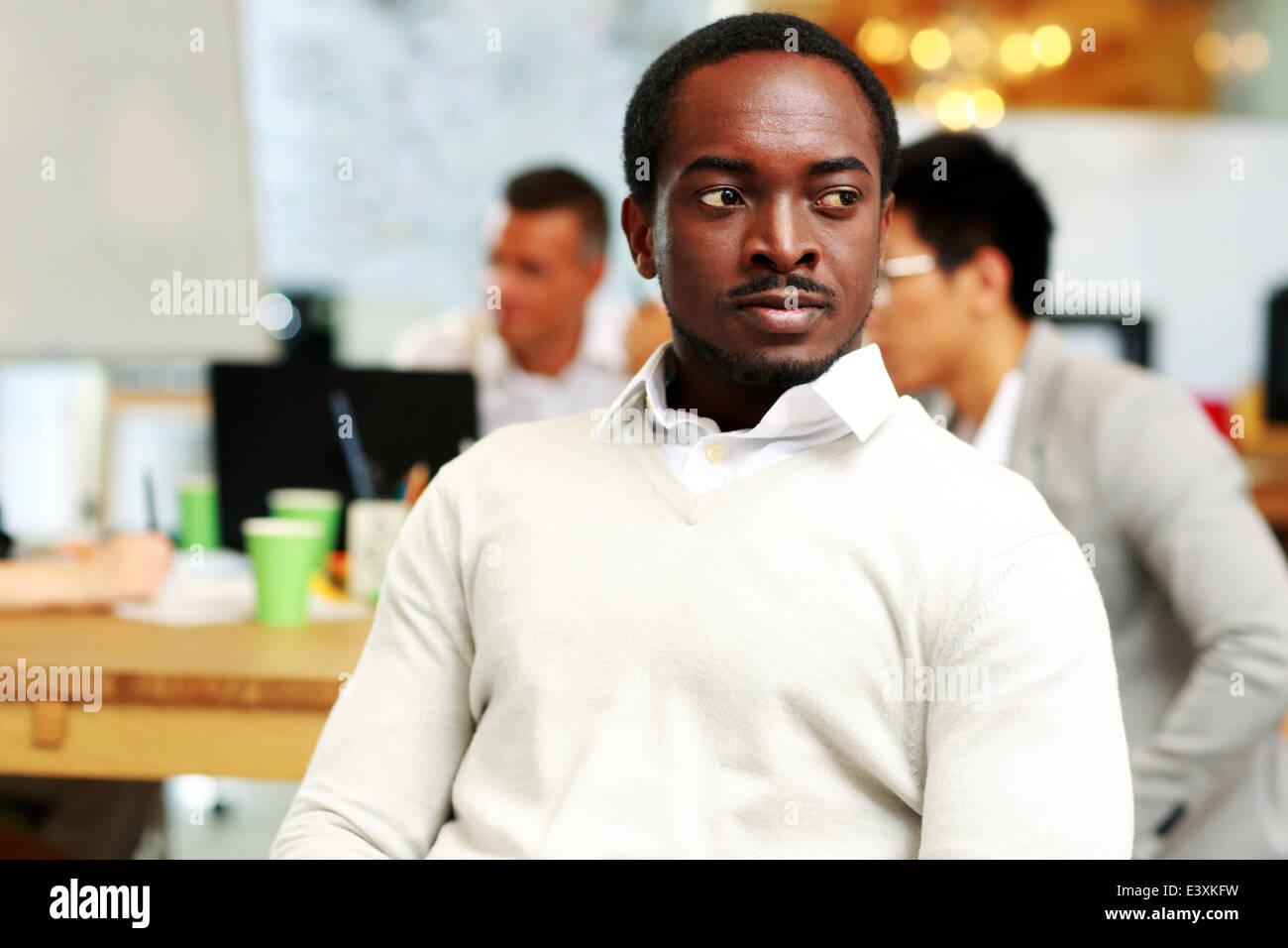 Ritratto di un pensieroso uomo africano che guarda lontano in office Immagini Stock