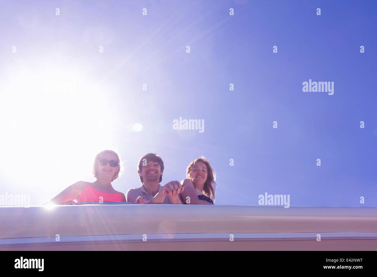 Ritratto di tre amici adulti guardando giù dal yacht Immagini Stock