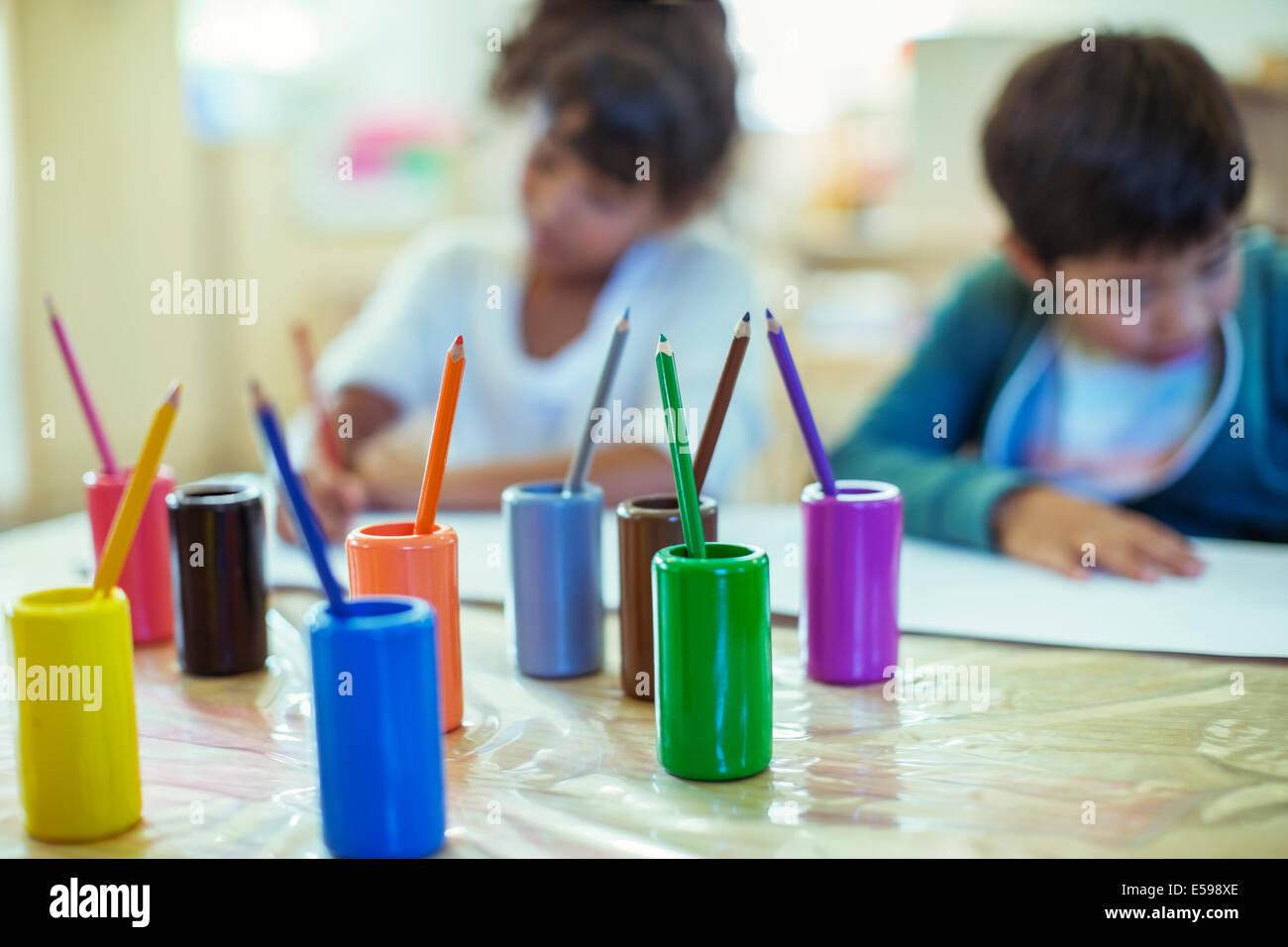Matite colorate su scrivania in aula Immagini Stock