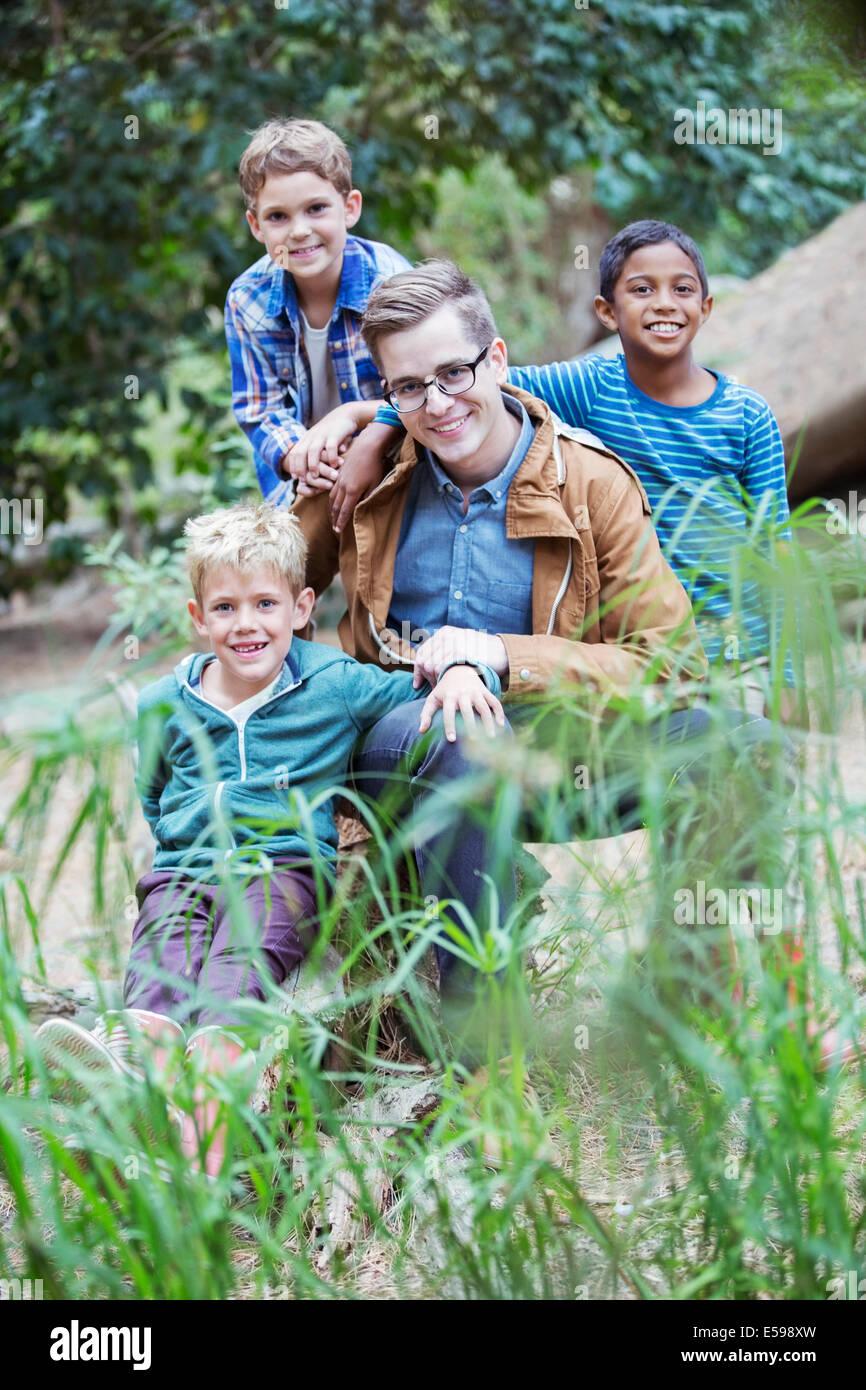 Gli studenti e il maestro sorridente in foresta Immagini Stock