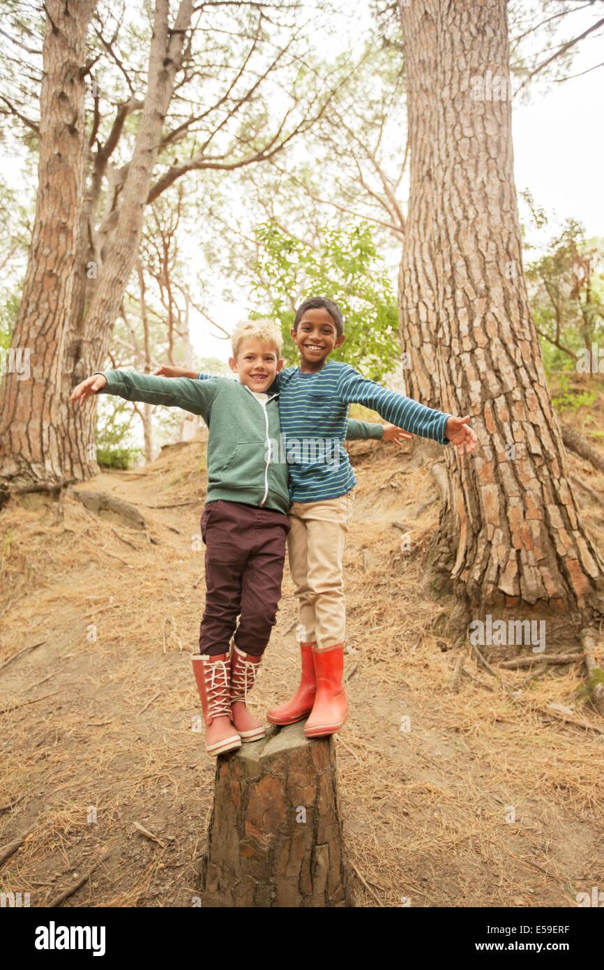 Arrampicata per bambini sul moncone in foresta Immagini Stock