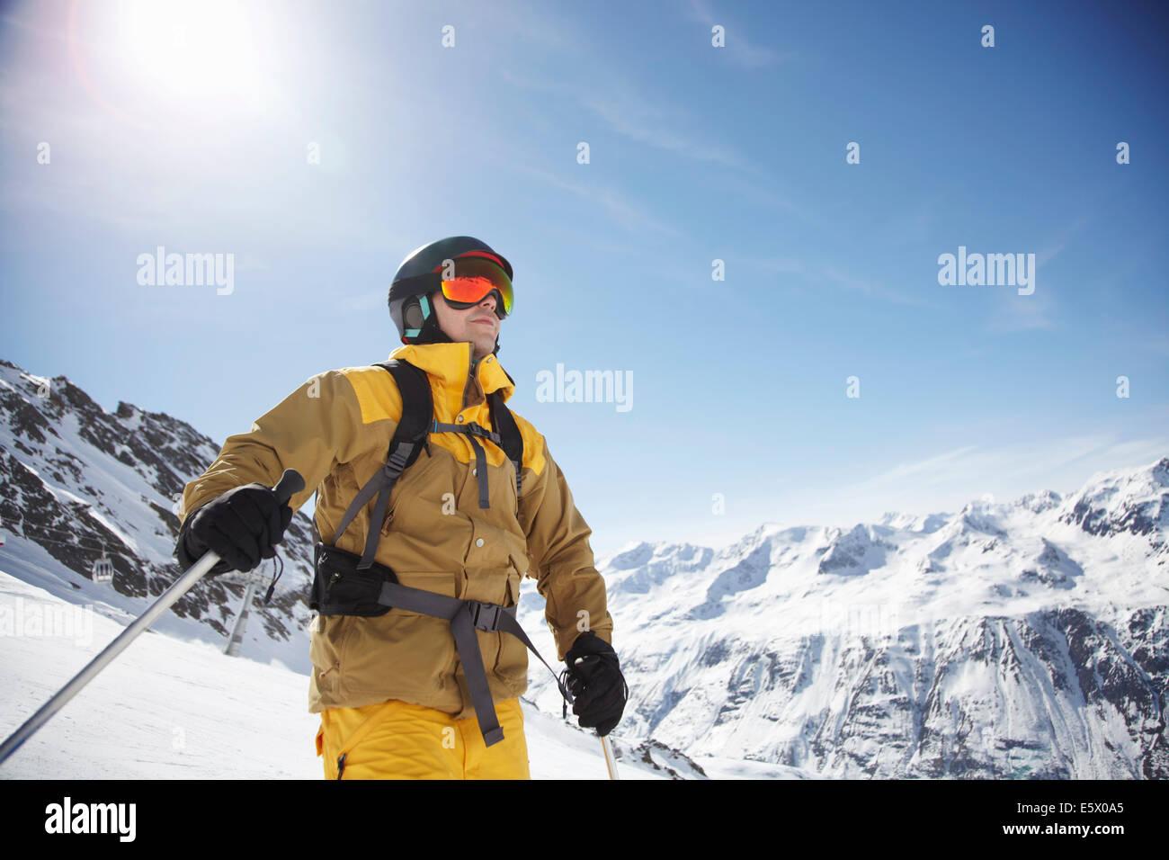 Basso angolo vista di metà maschio adulto sciatore sulla montagna, Austria Immagini Stock