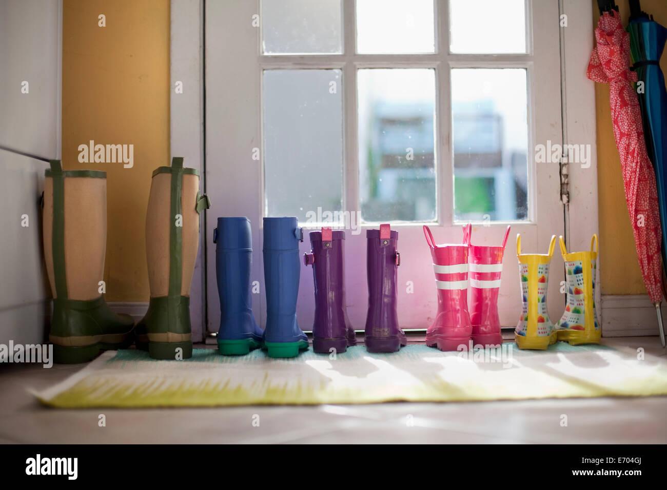Fila ordinata di stivali di gomma in corrispondenza della porta posteriore Immagini Stock