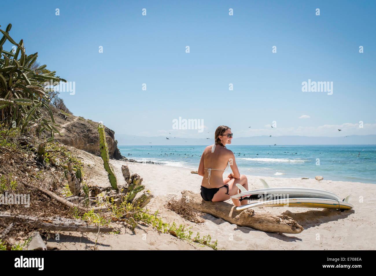 Giovane donna seduta su driftwood presso la spiaggia, le tavole da surf dal suo lato Immagini Stock