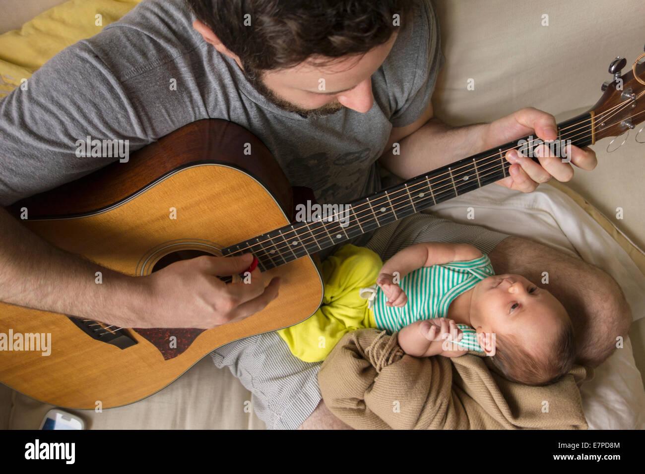 Padre suonare la chitarra per la figlia del neonato Immagini Stock