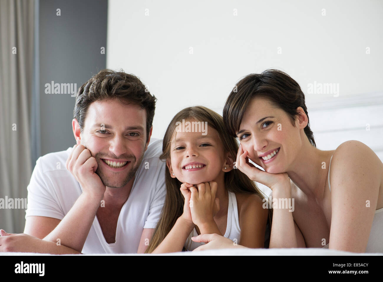 I genitori e la figlia giacente sul letto insieme, ritratto Immagini Stock