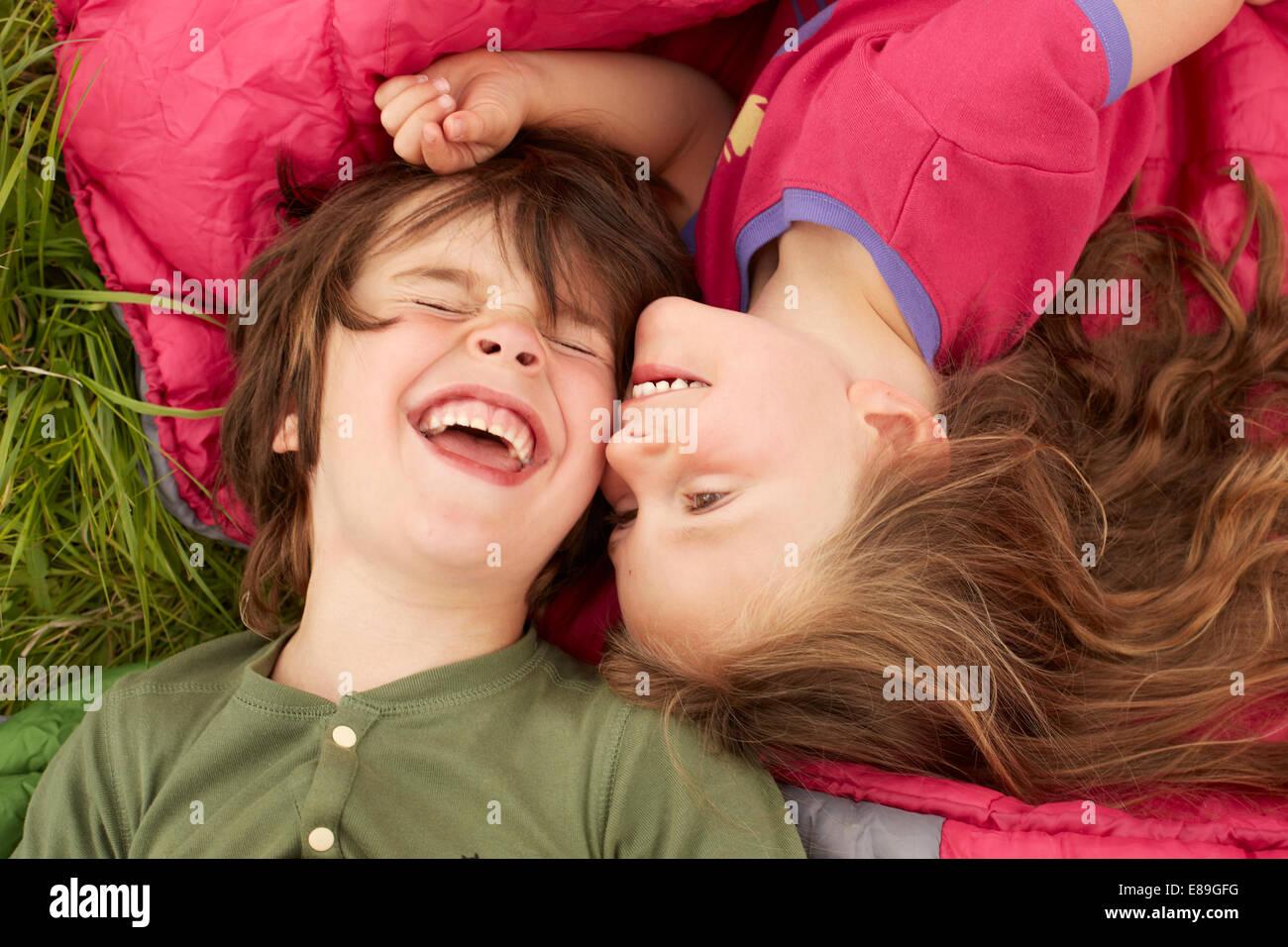 Un ragazzo e una ragazza ridere mentre posa su sacchi a pelo Immagini Stock