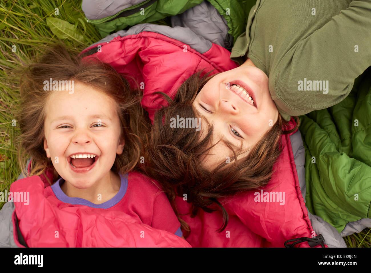 Ridere i bambini che posa in sacchi a pelo Immagini Stock