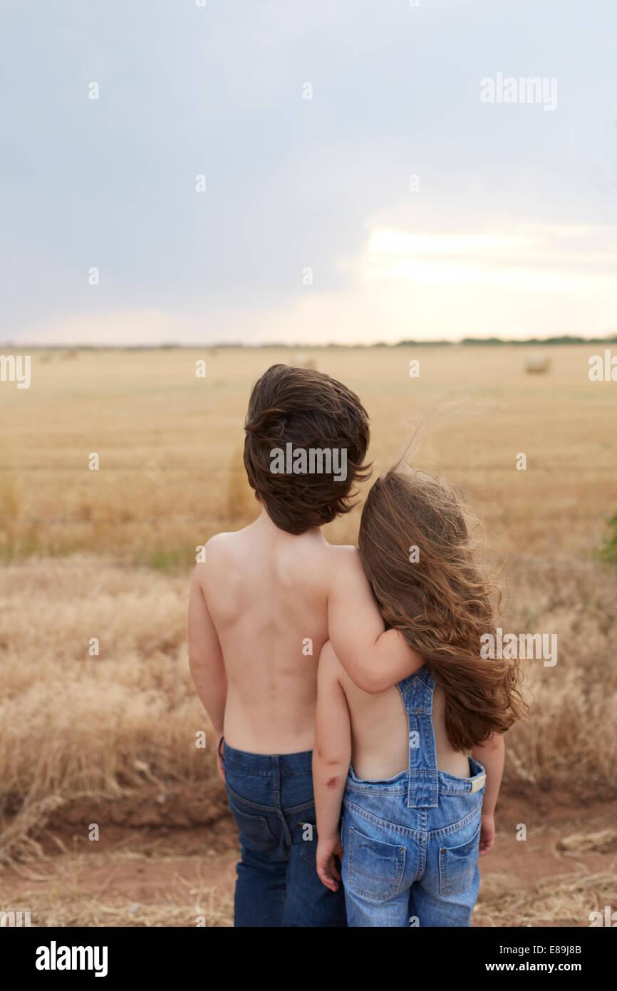 Un ragazzo e una ragazza che si affaccia su Campo paese Immagini Stock
