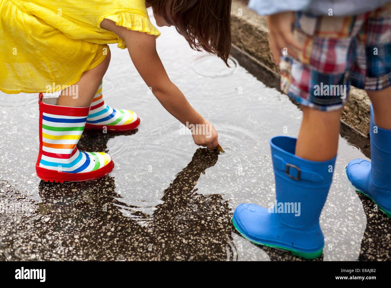 Ragazzo e sorella di indossare stivali di gomma guardando in giù in una pozza di pioggia Immagini Stock