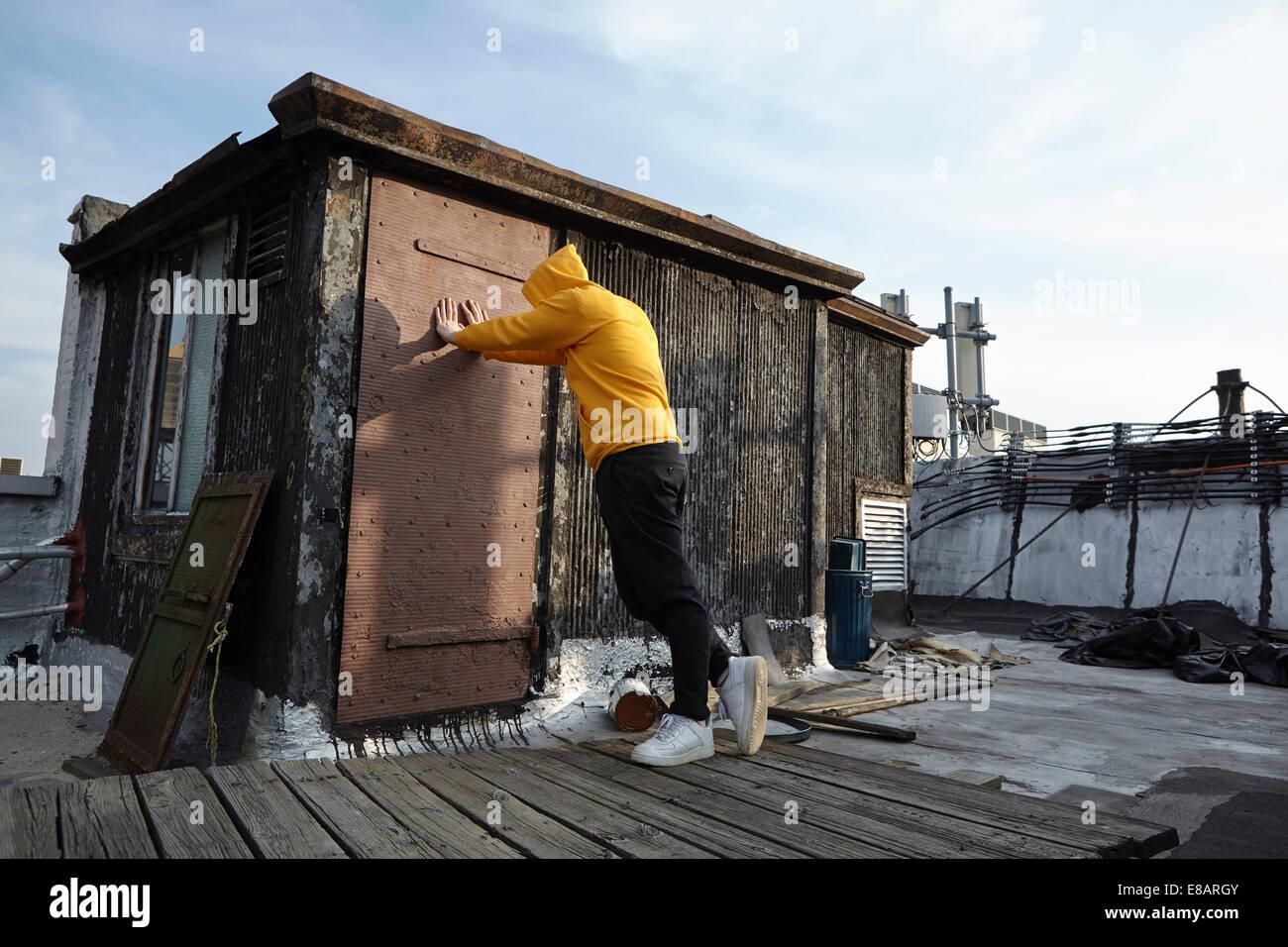 Giovane uomo appoggiato contro il tetto a capanna e guardando verso il basso Immagini Stock