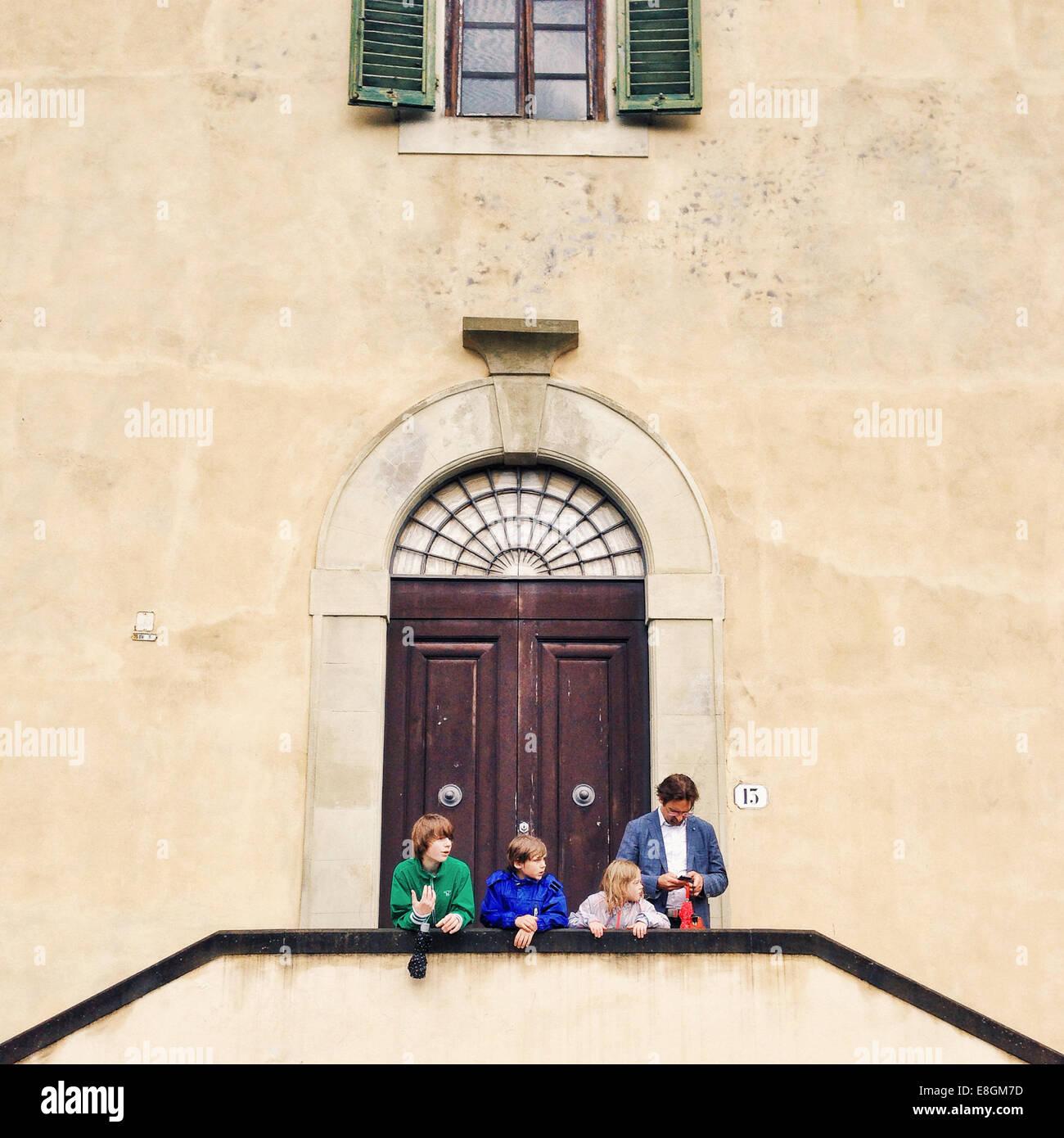 L'Italia, Firenze, padre di tre bambini (10-11, 12-13) in piedi nella parte anteriore dell'edificio Immagini Stock