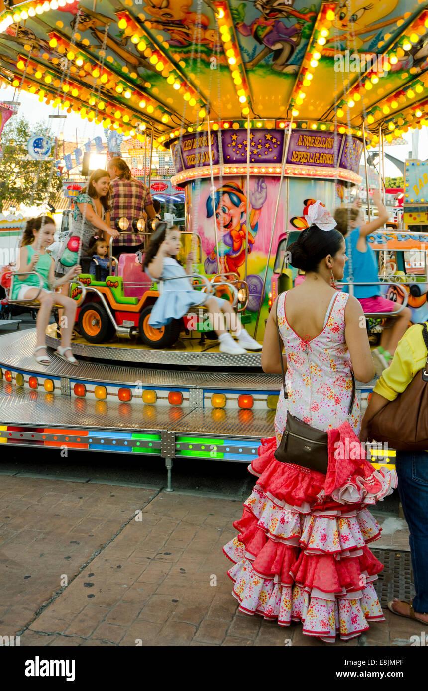 Donna spagnola nel tradizionale abito festivo in attesa accanto alla giostra chlidrens, merry-go-round a fiera annuale. Immagini Stock