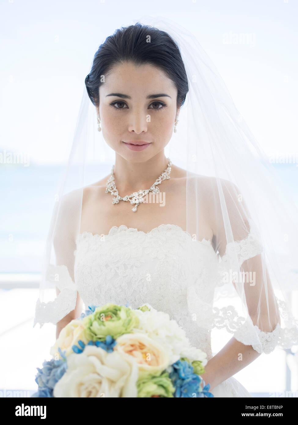 Razza mista, Asian / American sposa in bianco abito da sposa in spiaggia tropicale di nozze di destinazione Immagini Stock