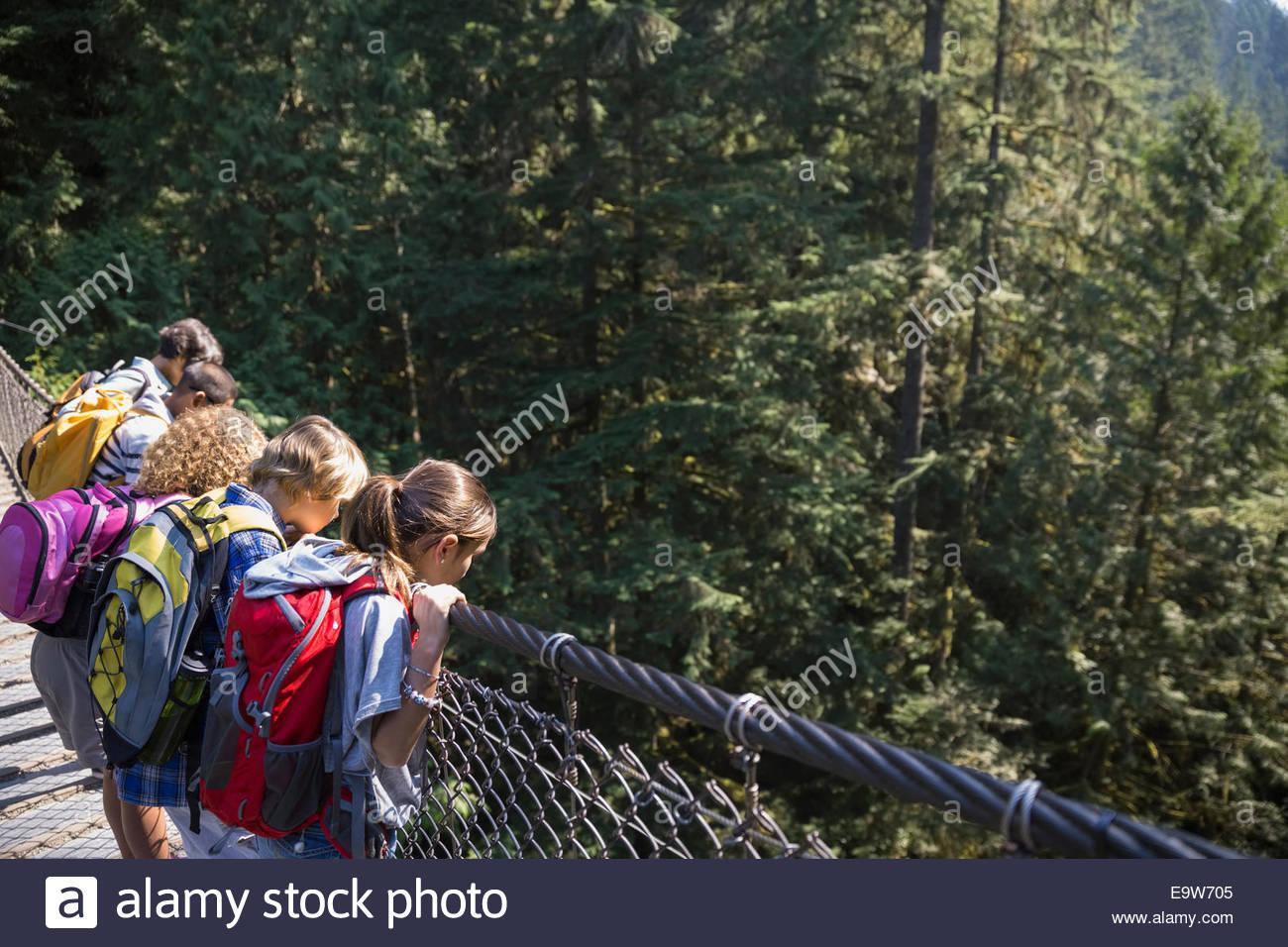 I bambini con zaini guardando giù dal ponte pedonale Immagini Stock