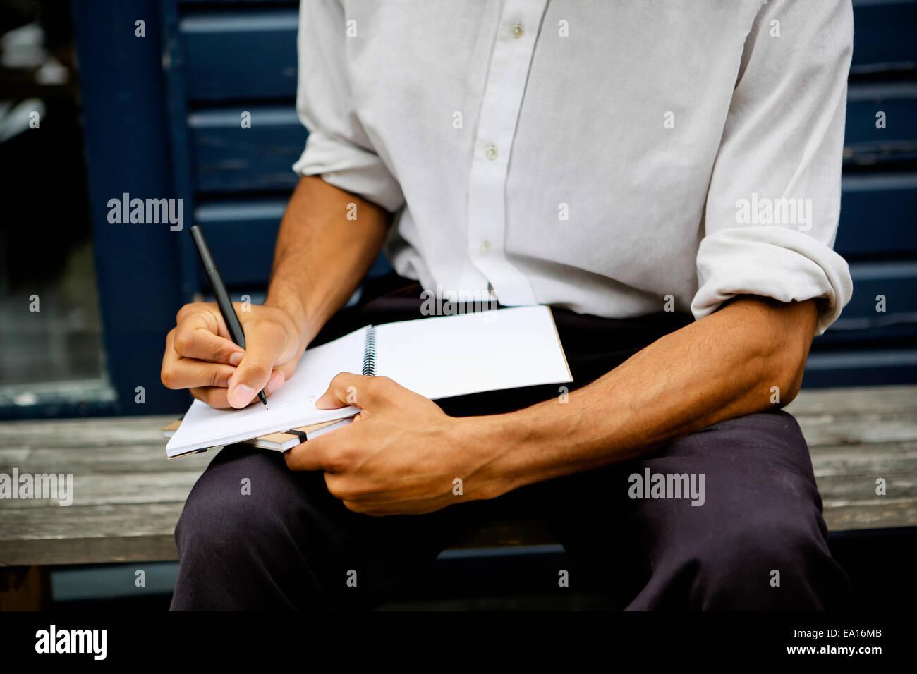 L'uomo la scrittura in notebook Immagini Stock