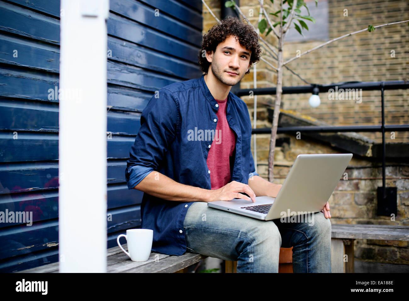 Uomo con notebook sul banco di lavoro Immagini Stock