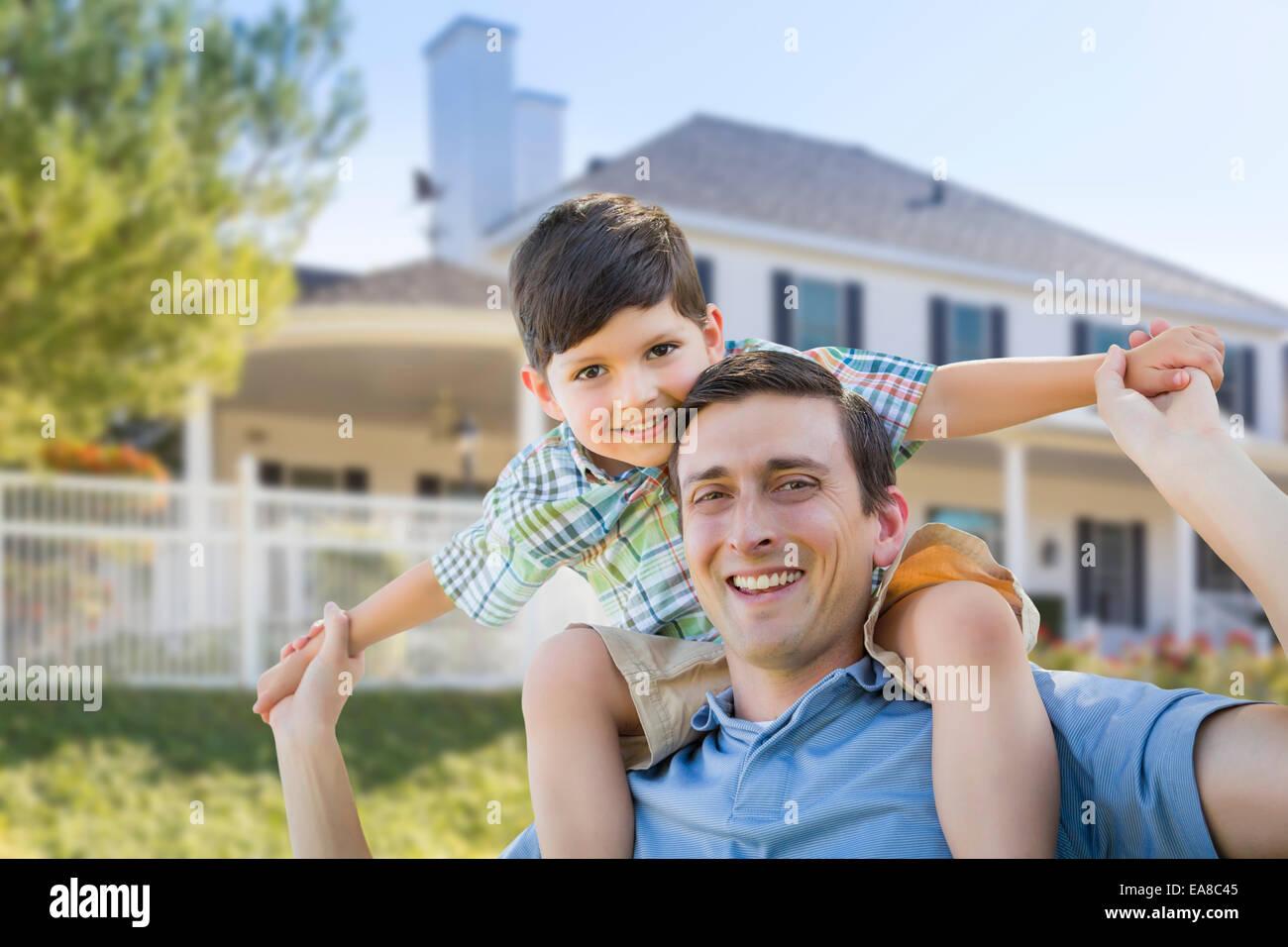 Razza mista padre e figlio giocando Piggyback davanti alla loro casa. Immagini Stock