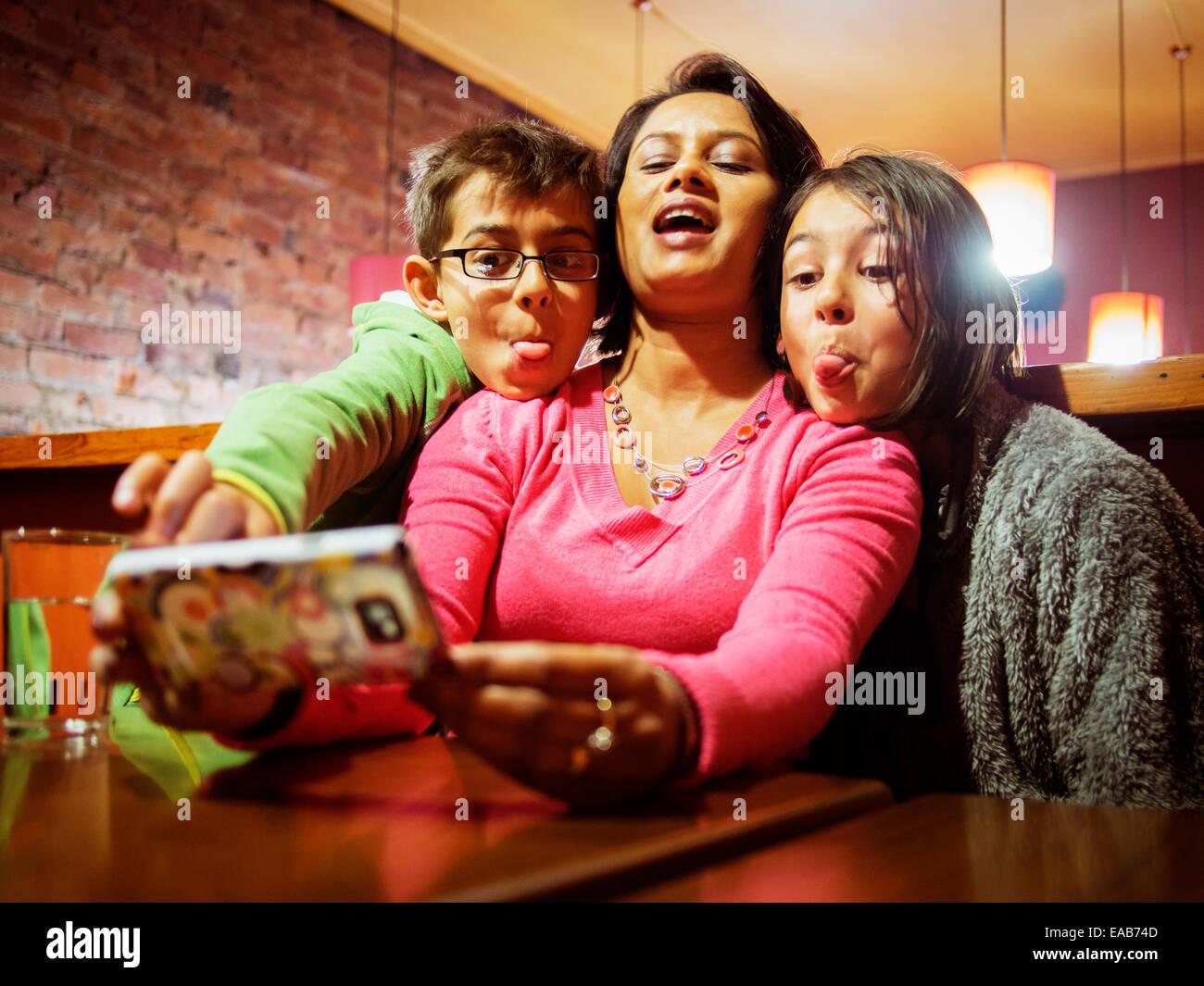 Donna assume selfie sul telefono. Figlia di madre e figlio. Immagini Stock