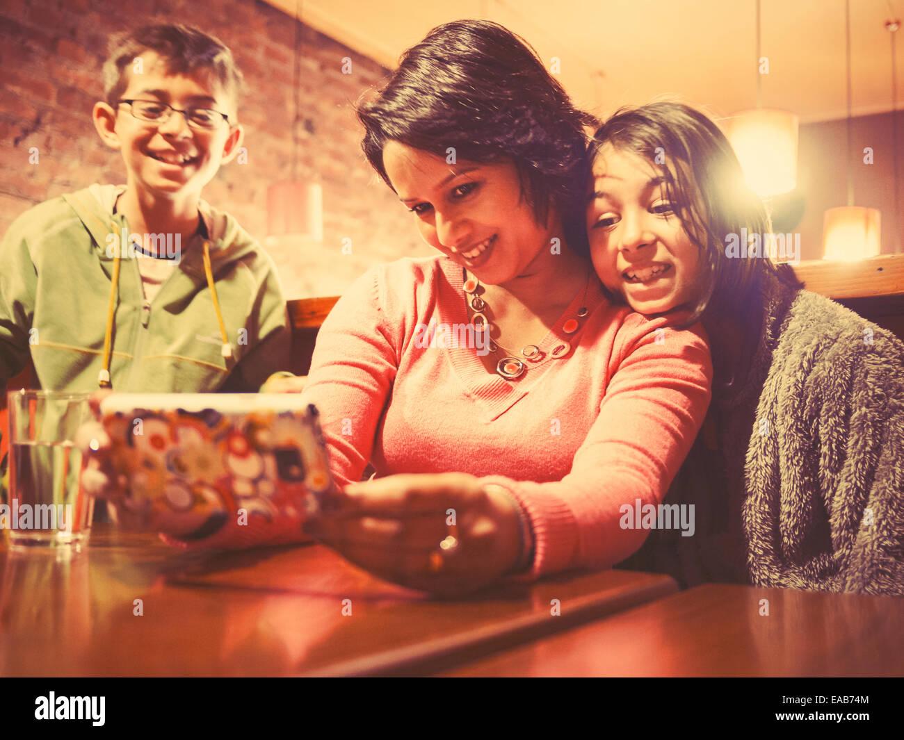 Donna assume immagine di sé e la figlia mentre figlio orologi Immagini Stock