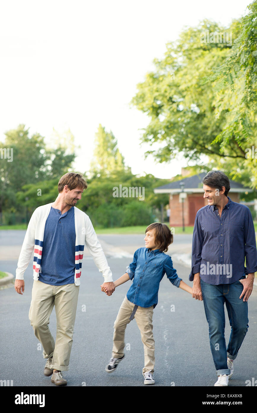 Ragazzo a piedi con i suoi padri all'aperto Immagini Stock
