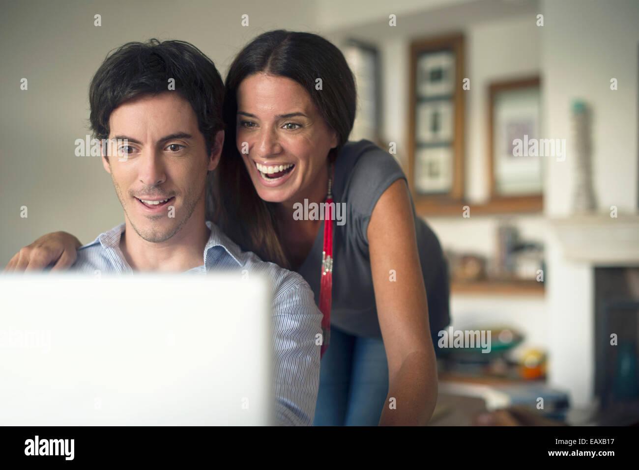 Giovane guardando al computer portatile insieme Immagini Stock