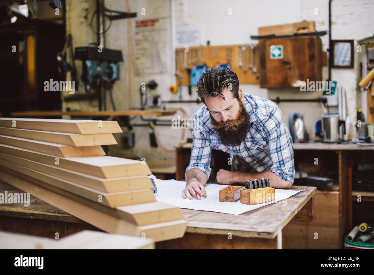 Adulto medio artigiano guardando in giù a blueprint in organo workshop Immagini Stock