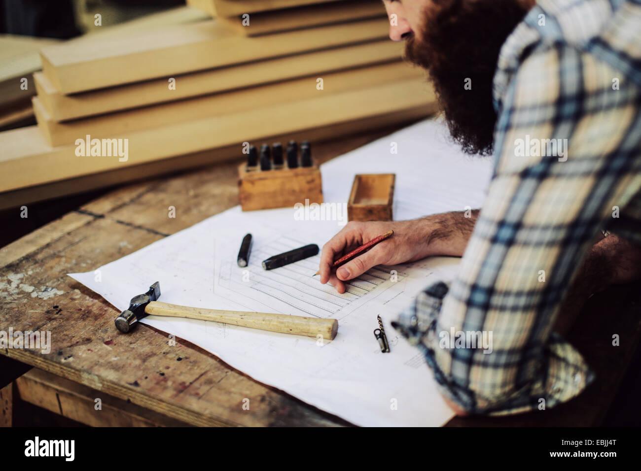 Ritagliato colpo di metà adulto artigiano guardando in giù a blueprint in organo workshop Immagini Stock