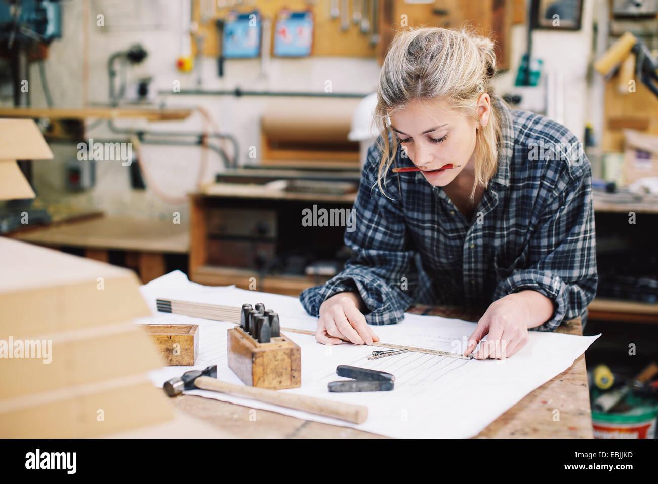Giovani craftswoman blueprint di misurazione su un banco di lavoro in organo a canne workshop Immagini Stock