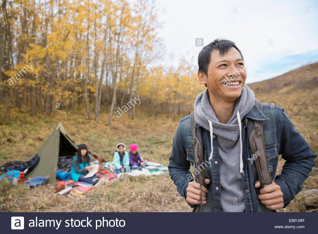 Uomo sorridente campeggio con la famiglia Immagini Stock