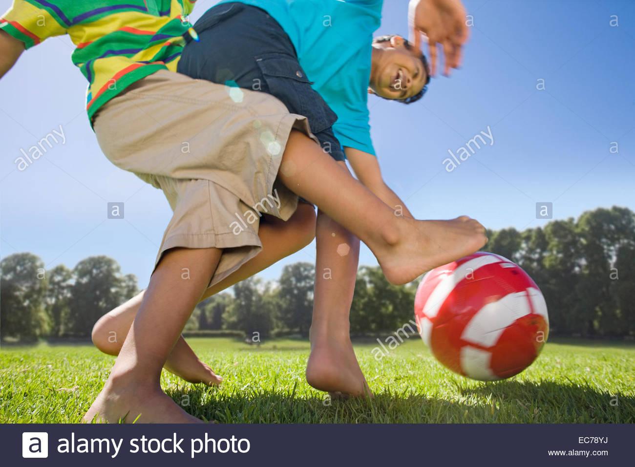 Sorridenti ragazzi che giocano a calcio in posizione di parcheggio Immagini Stock