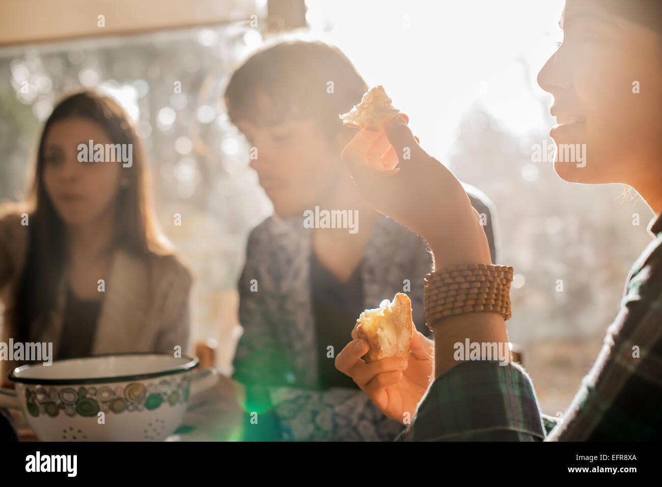 Tre persone sedute a un tavolo, sorridente, mangiare e chat. Immagini Stock