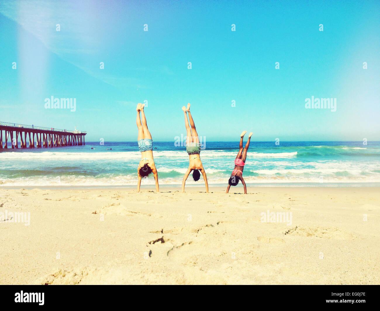 Madre, padre e figlia facendo handstand sulla spiaggia Immagini Stock