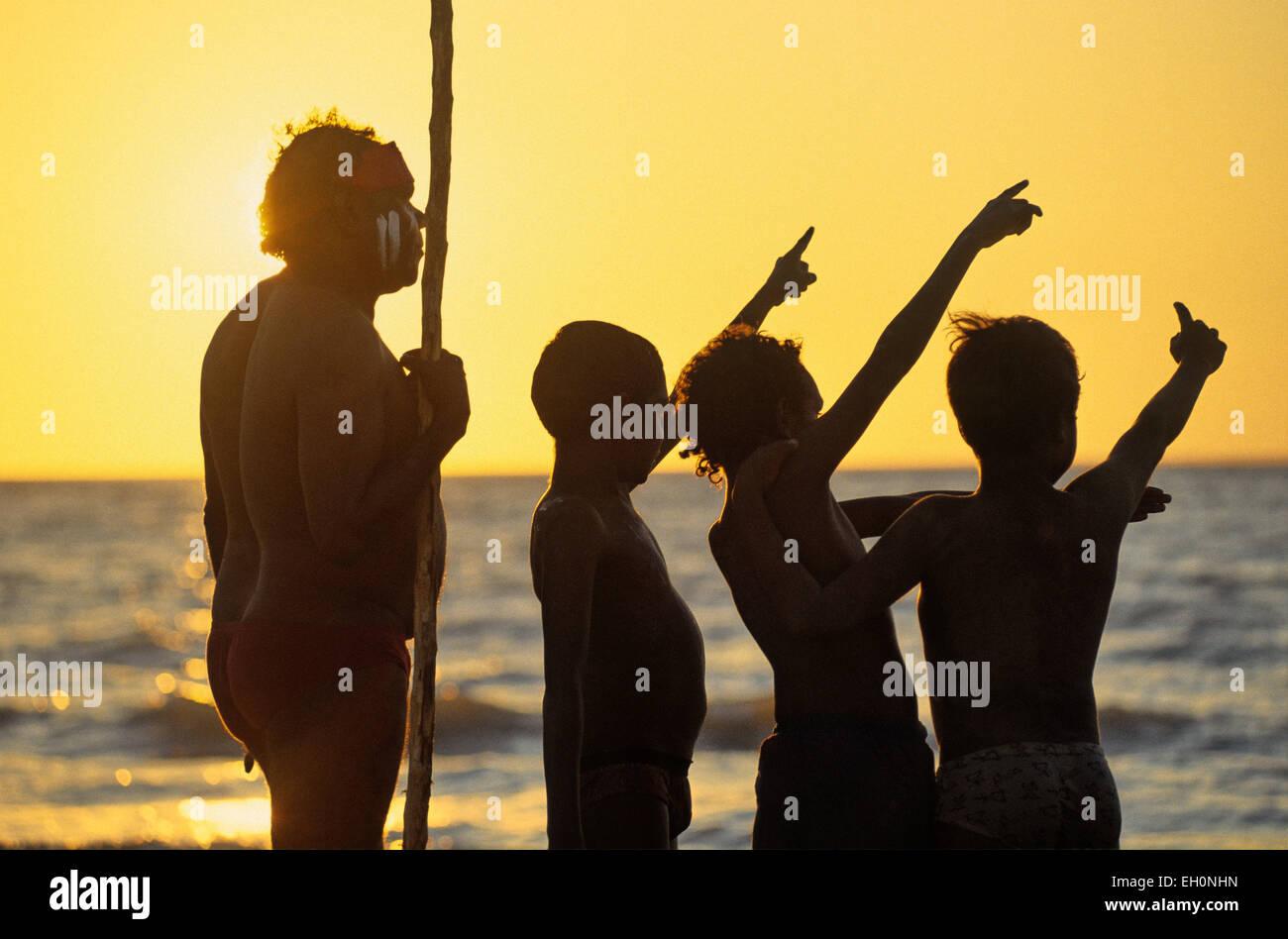 Aborigeno con un polo e bambini puntando verso il cielo al tramonto, Darwin, in Australia Immagini Stock