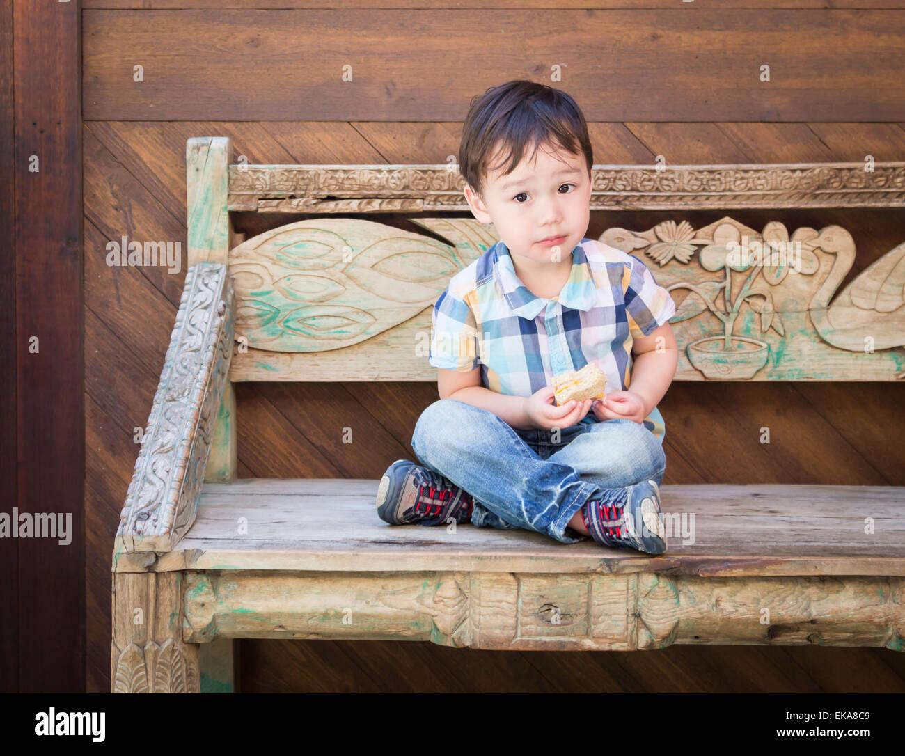 Carino rilassata razza mista ragazzo seduto sul banco di mangiare il suo panino. Immagini Stock