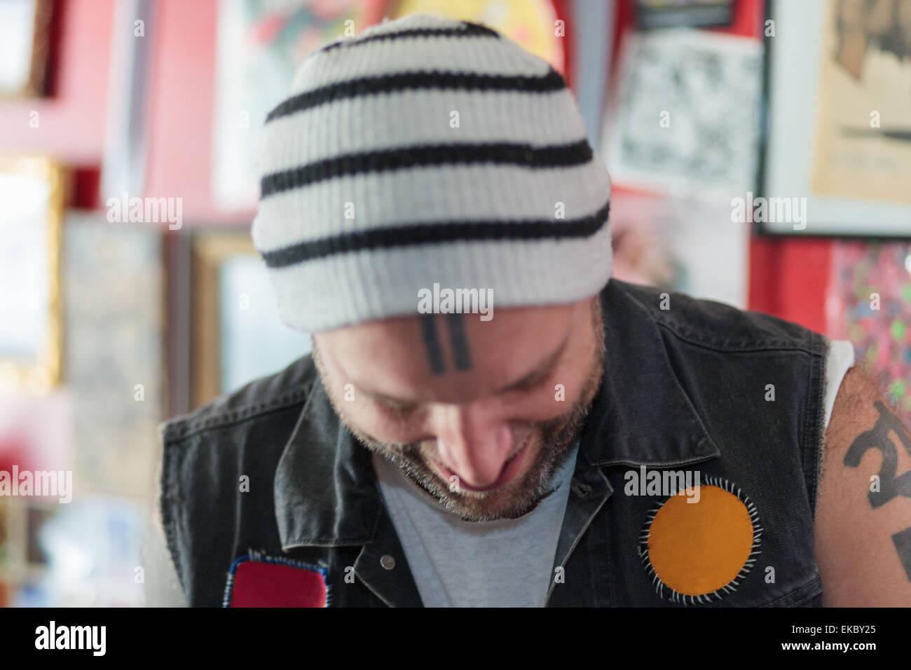 Close up dei maschi di punk negoziante sorridente e guardando verso il basso nel giocattolo vintage shop Immagini Stock