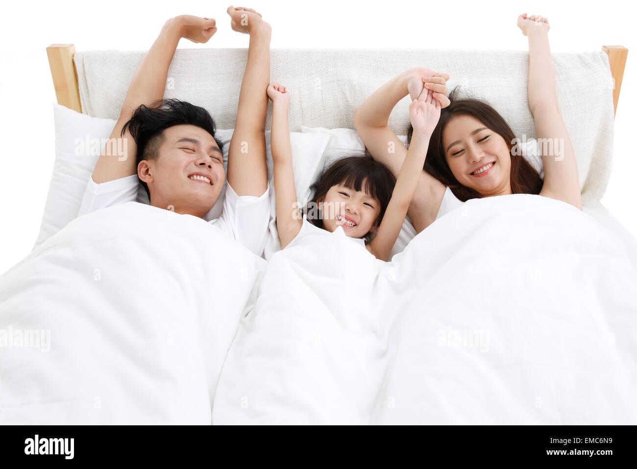 La felicità di una famiglia di tre persone nel letto della camera da letto si è svegliato Immagini Stock