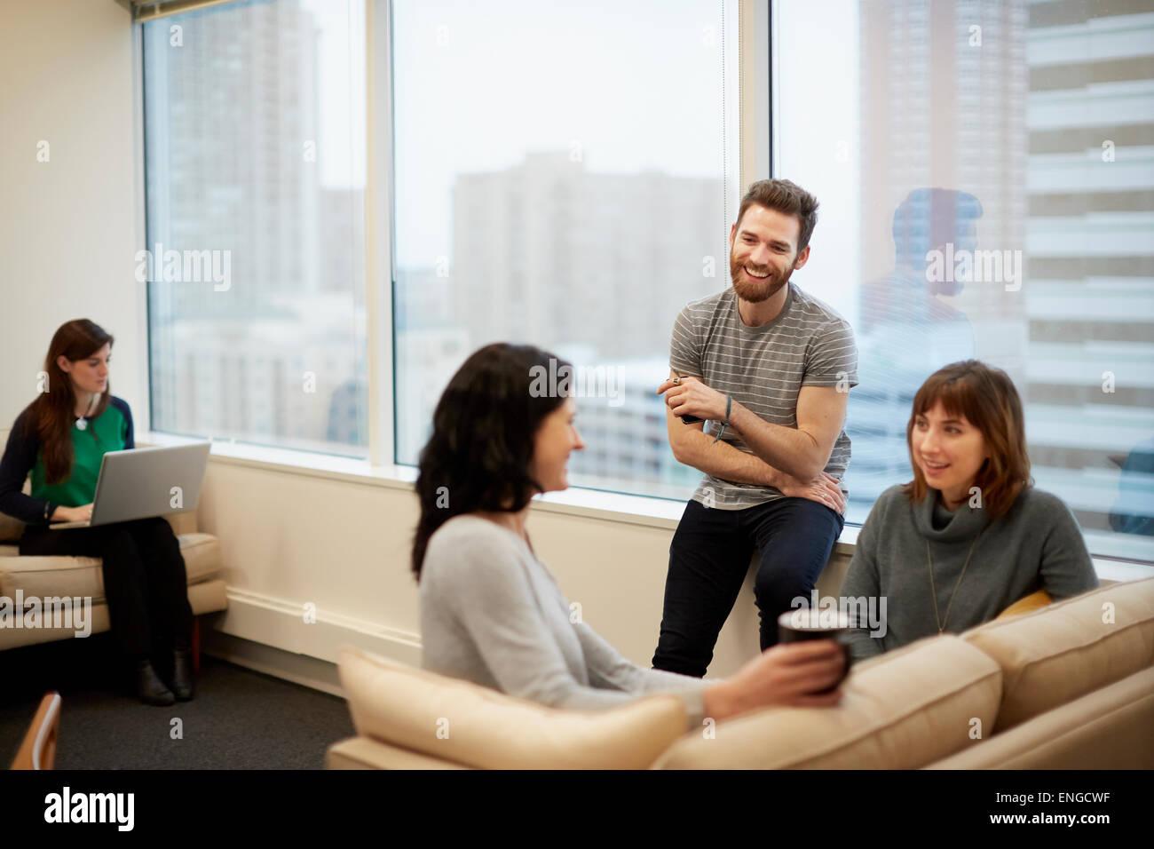 Tre persone da una finestra in un ufficio, due donne e un uomo. Immagini Stock